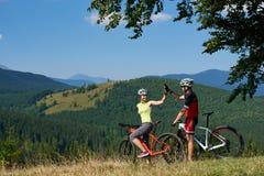 Szczęśliwi rowerzyści dobierają się, mężczyzna i kobiety pod dużą zieloną gałąź pozycja z rowerami na trawiastym wzgórzu, zdjęcia royalty free