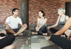 Szczęśliwi roześmiani młodzi ludzie relaksuje po trenować zdjęcia stock