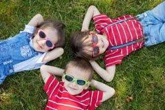 Szczęśliwi rozochoceni uśmiechnięci dzieci, kłaść na trawie, być ubranym śpiewam obraz stock