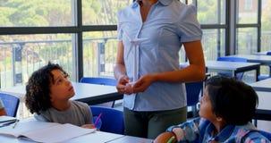 Szcz??liwi schoolkids oddzia?a wzajemnie z nauczycielem przy biurkiem w sali lekcyjnej 4k zdjęcie wideo