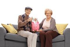 Szczęśliwi seniory stawia pieniądze w piggybank i patrzeje Obrazy Royalty Free