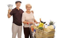 Szczęśliwi seniory z pieniędzy plikami i wózek na zakupy groce pełno Zdjęcie Royalty Free