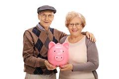 Szczęśliwi seniory z piggybank Fotografia Royalty Free