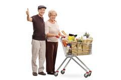 Szczęśliwi seniory z wózek na zakupy daje aprobatom Zdjęcie Stock