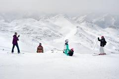 Szczęśliwi snowboarders i narciarki cieszą się na górze góry Fotografia Royalty Free