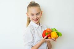 Szczęśliwi sprawności fizycznej dziewczyny mienia warzywa odizolowywający Fotografia Royalty Free
