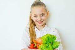 Szczęśliwi sprawności fizycznej dziewczyny mienia warzywa odizolowywający Zdjęcie Stock