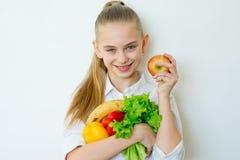 Szczęśliwi sprawności fizycznej dziewczyny mienia warzywa odizolowywający Fotografia Stock