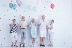 Szczęśliwi starsi ludzie świętuje przyjaciela ` s urodziny z kolorowymi balonami zdjęcie stock