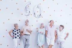 Szczęśliwi starszego mężczyzna i kobiety mienia srebra balony zdjęcie stock