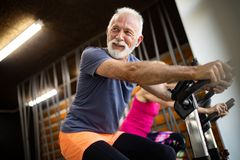 Szczęśliwi starszy ludzie robi ćwiczeniom w gym zostawać dostosowywający obrazy royalty free