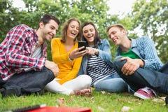 Szczęśliwi studenci collegu patrzeje telefon komórkowego w parku Obrazy Royalty Free