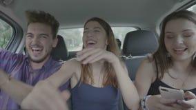 Szczęśliwi szaleni przyjaciele tanczy i śmia się z tyłu napędowego taxi samochodu podczas gdy one wiszący za - zbiory