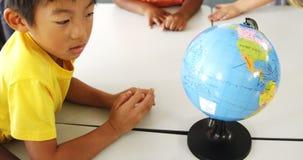 Szczęśliwi szkoła dzieciaki z kulą ziemską w sala lekcyjnej zbiory wideo