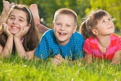szczęśliwi trawa dzieciaki trzy fotografia royalty free
