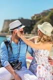 Szczęśliwi turyści odpoczywa przy doc podczas gdy badający miasto wpólnie fotografia stock