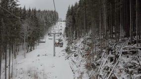 Szczęśliwi turyści poruszający na długim narciarskim dźwignięciu w Carpathians w zimie w mo zbiory wideo