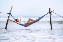 Szczęśliwi uśmiechnięci kobiet kłamstwa w hamak huśtawce nad oceanem surfują li Obrazy Royalty Free