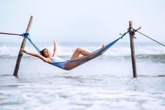 Szczęśliwi uśmiechnięci kobiet kłamstwa w hamak huśtawce nad oceanem surfują li Zdjęcia Royalty Free