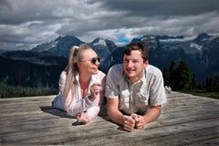 Szczęśliwi uśmiechnięci ludzie obozuje w górach Para małżeńska na namiotowym ochraniaczu ma zabawę i relaksować fotografia stock