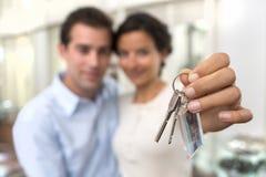 Szczęśliwi uśmiechnięci potomstwa dobierają się pokazywać klucze ich nowy dom fotografia royalty free