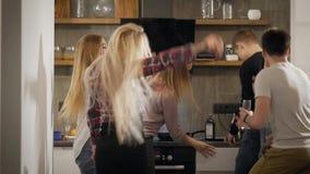 Szczęśliwi ucznie są relaksujący na domu przyjęciu na kuchni w schronisku, słuchający modna muzyka i taniec zbiory
