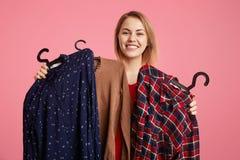 Szczęśliwi uroczy młoda kobieta chwyty odziewają na wieszakach, radują się nowego zakup, doesn ` t znają co wybierać, iść wydawać obraz royalty free