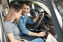 Szczęśliwi właściciele samochodu. Piękni potomstwa dobierają się obsiadanie przy przodu se Fotografia Stock