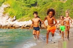 Szczęśliwi wieloetniczni dzieciaki biega wzdłuż piaskowatej plaży zdjęcia stock