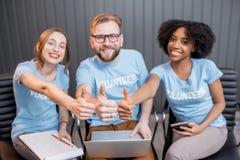 Szczęśliwi wolontariuszi indoors zdjęcia royalty free