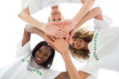 Szczęśliwi wolontariuszi stawia ręki wpólnie i patrzeje w dół przy kamerą Fotografia Royalty Free