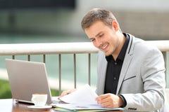 Szczęśliwi wykonawczy czytanie dokumenty w barze obraz stock