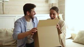 Szczęśliwi z podnieceniem para klienci otwierają kartonu obsiadanie na kanapie zbiory wideo