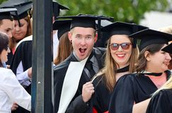 Szczęśliwi z podnieceniem studenci uniwersytetu kończy studia skalowanie dzień obraz stock