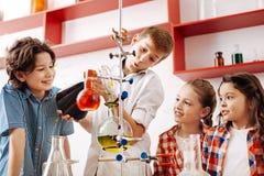 Szczęśliwi zadowoleni dzieciaki eksperymentuje z chemicznymi cieczami fotografia stock