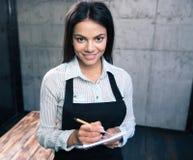 Szczęśliwy ładny żeński kelner w fartuchu zdjęcia royalty free