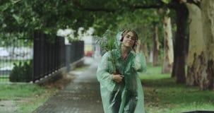 Szczęśliwy ładny ladie odprowadzenie na ulicie na podeszczowym dniu trzyma zielonego kwiatu słuchającej muzyki od hełmofonów i zdjęcie wideo