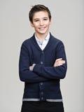 Szczęśliwy ładny nastoletni chłopak pozuje przy studiiem Zdjęcia Stock