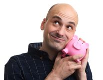 Szczęśliwy łysy mężczyzna trzyma prosiątko banka zdjęcia royalty free