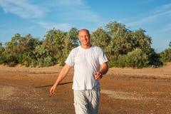 Szczęśliwy łysy mężczyzny odprowadzenie na plaży w biel ubraniach obrazy royalty free