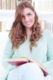 Szczęśliwy śliczny brunetki obsiadanie na leżance czyta książkę w jaskrawym li Zdjęcia Royalty Free