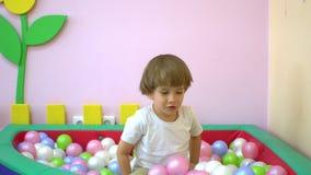 Szczęśliwy śliczny chłopiec berbeć ono uśmiecha się i bawić się w wielo- coloured balowym basenie preschool zbiory wideo