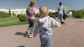 Szczęśliwy śliczny chłopiec bieg dla matki w zieleń parku, jego stara siostra biega przy zarygluj sk?adu poj?cia rodziny orzechy zbiory