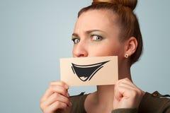 Szczęśliwy śliczny dziewczyny mienia papier z śmiesznym smiley rysunkiem Zdjęcie Royalty Free