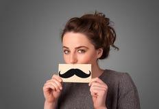 Szczęśliwy śliczny dziewczyny mienia papier z wąsy rysunkiem Fotografia Stock