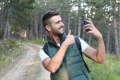 Szczęśliwy śliczny mężczyzna robi selfie fotografii na smartphone i pokazuje kciuk up nad natury tłem lasu lub drewien Obrazy Stock