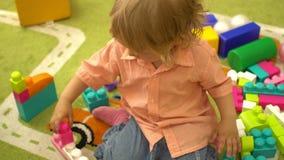 Szczęśliwy śliczny preschool dziecko bawić się z wielo- coloured elementami w dziecinu Edukacja w przedszkolu zbiory