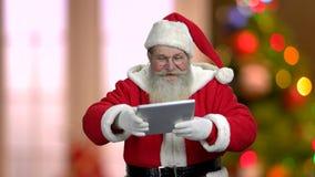 Szczęśliwy Święty Mikołaj pokazuje cyfrową pastylkę zbiory