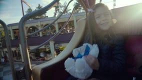 Szczęśliwy żeński dziecko w przyciąganie parku ma zabawę na carousel trochę słodka dziewczyna zdjęcie wideo