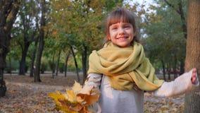 Szczęśliwy żeński dziecko z kolorem żółtym opuszcza falowanie rękę na kamerze i uśmiechu przy parkiem zbiory wideo